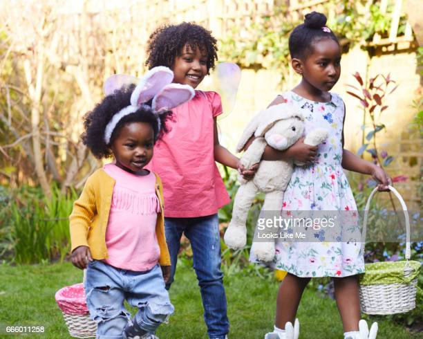 children on an easter egg hunt. - chasse aux oeufs de paques photos et images de collection