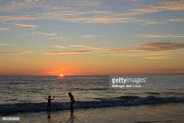 Children on atlantic beach. Sunset.