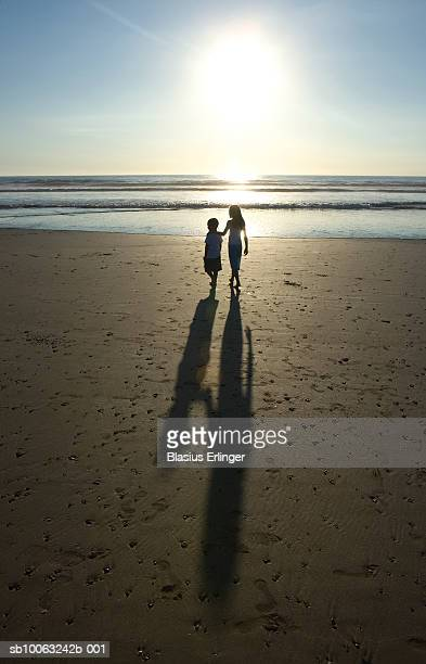 children on beach at dusk, rear view - blasius erlinger stock pictures, royalty-free photos & images
