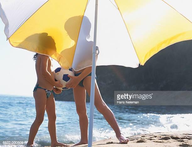 Children on Beach by Umbrella