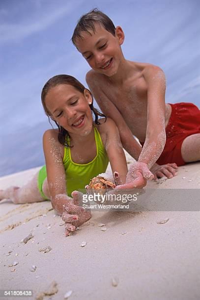 Children on Beach Holding Hermit Crab