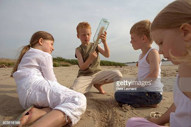 Children on Beach Inspecting Message in a Bottle