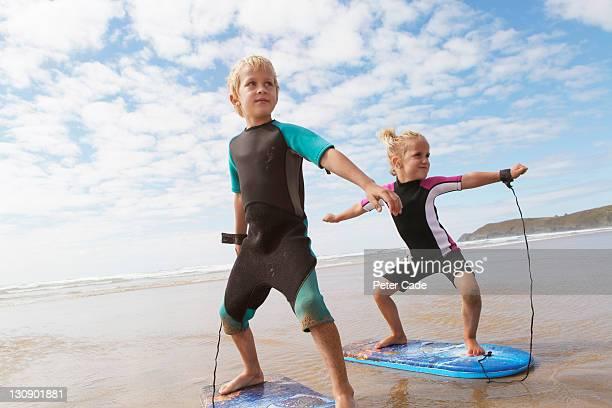 children on beach pretending to surf