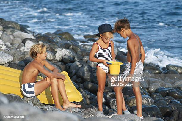 Children (6-11) on beach with bucket and airbed