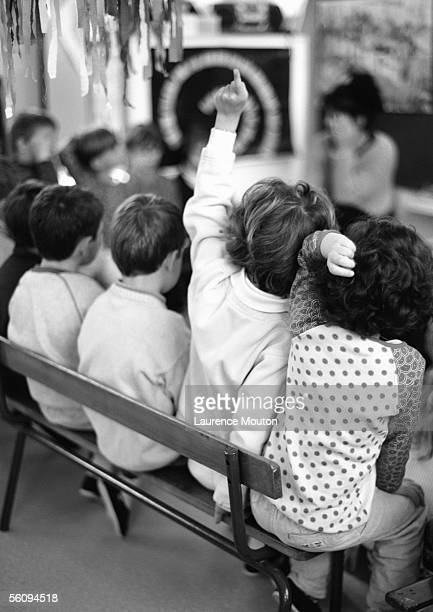 Children on bench, one putting finger up, rear view, bow