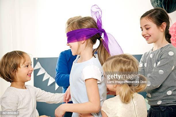 Children on birthday party playing Blind Man's Bluff, Munich, Bavaria, Germany