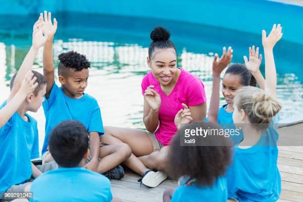 Children on field trip at marine park, raising hands