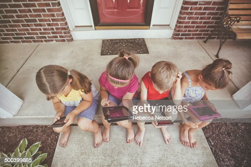 Children on front stoop using electronic devices