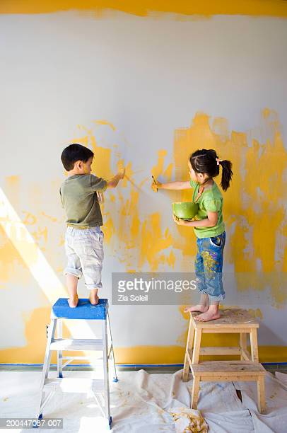 Children (2-6) on ladders painting wall, rear view
