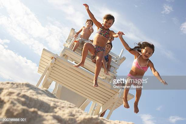 Children (5-11) on life guard's platform, two girls jumping off