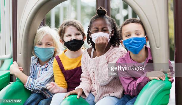 children on playground wearing face masks, covid-19 - coronavirus mask stock pictures, royalty-free photos & images