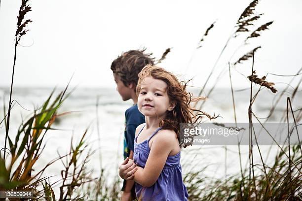 children on sand dune watching ocean