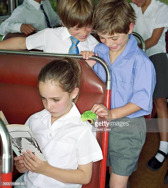 Children (6-10) on school bus, boy placing toy frog on girl's shoulder