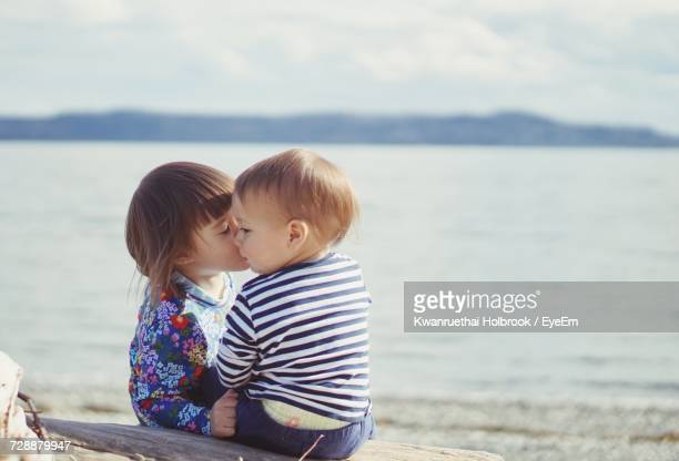 children on sea shore against sky - teenage couple stock photos and pictures