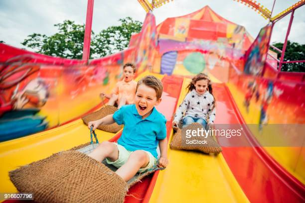 children on slide at a funfair - traveling carnival stock pictures, royalty-free photos & images