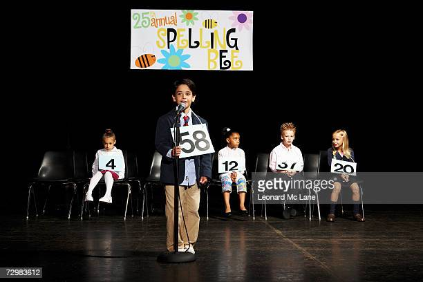 children (6-9) on stage at spelling bee, boy at microphone - あがり症 ストックフォトと画像
