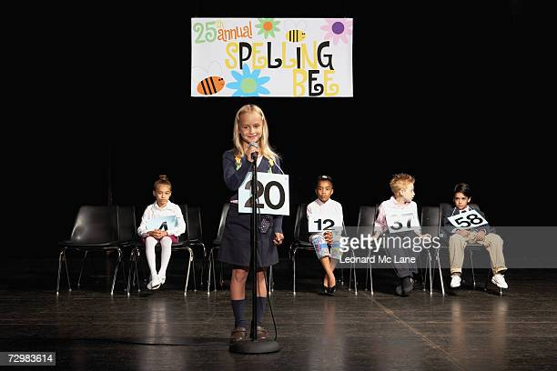 children (6-9) on stage at spelling bee, girl at microphone - あがり症 ストックフォトと画像