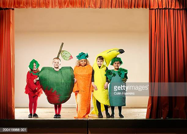 children (4-6) on stage wearing fruit and vegetable costumes, portrait - acting performance stock pictures, royalty-free photos & images