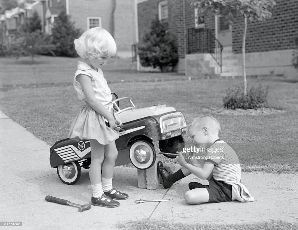 Children on suburban sidewalk, boy playing as mechanic, oiling toy pedal car. : Stock-Foto