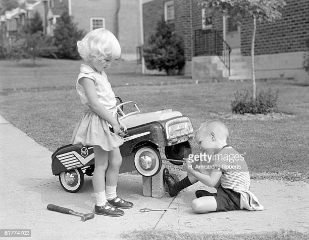 children on suburban sidewalk, boy playing as mechanic, oiling toy pedal car. - 1960 stock pictures, royalty-free photos & images
