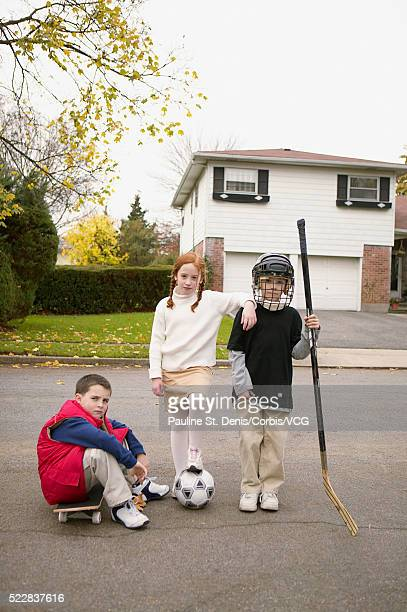 Children on suburban street with sports equipment