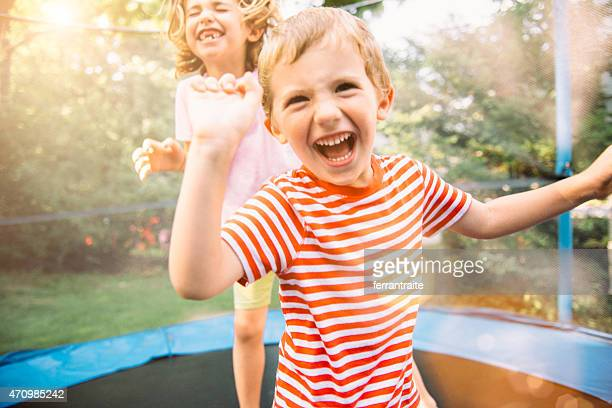 children on summer holidays jumping on trampoline - girl strips stock pictures, royalty-free photos & images