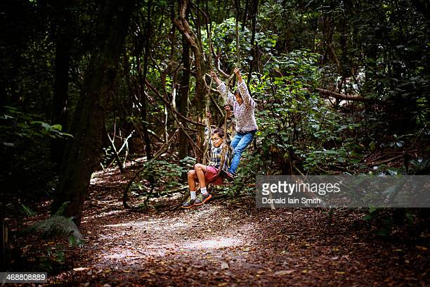 Children on swing in woods