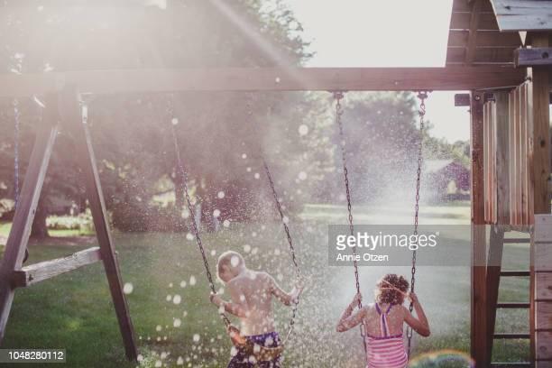 Children on Swing Set on Summer Day