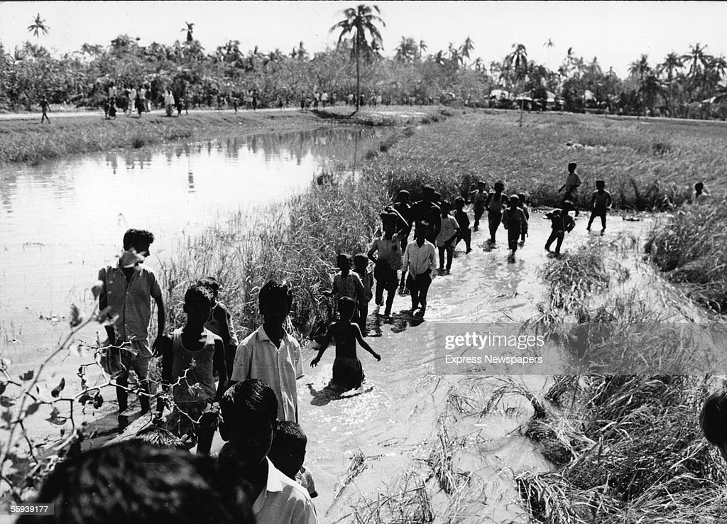 Children on the island of Bhola wade through floodwater after a tropical cyclone and tidal wave hit the area on November 13, 1970, which killed an estimated 200,000 to half a million people, with at least 100,000 missing, in East Pakistan (now Bangladesh), Bhola Island, East Pakistan, November 18, 1970.
