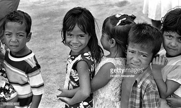 Children on the island of Pohnpei in the West Pacific Ocean wait to talk with a US Navy petty officer dressed as Santa Claus In the 1970s Navy...
