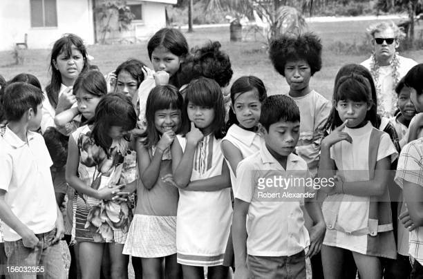 Children on the island of Tinian in the West Pacific Ocean wait to talk with a US Navy petty officer dressed as Santa Claus In the 1970s Navy...