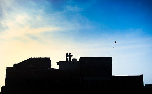 Children on the rooftop play with kites. 982873516