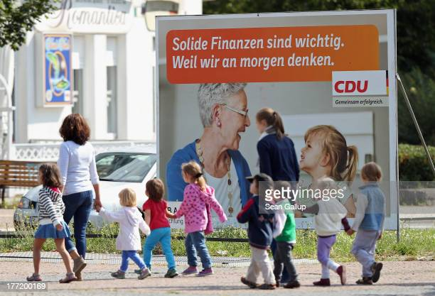 Children on their way to daycare walk past an election campaign poster of the German Christian Democrats that reads 'Solid Finances are important...