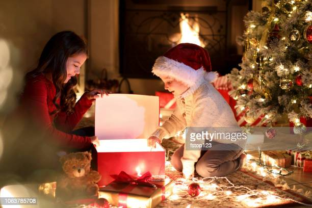 children open presents during christmas season near tree. - christmas gifts stock photos and pictures