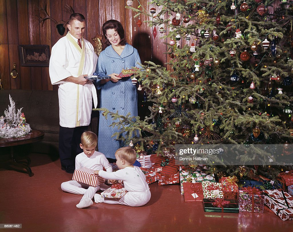 Children Opening Christmas Gifts While Parents Smile Stock Photo ...