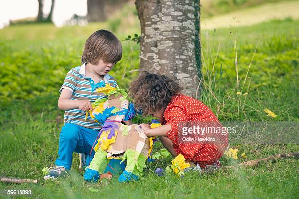 children opening pinata at party - colin hawkins stock pictures, royalty-free photos & images