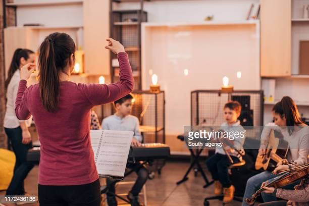 children orchestra in music school - rehearsal stock pictures, royalty-free photos & images