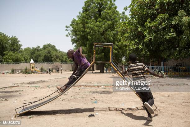 TOPSHOT Children orphaned by Boko Haram Islamists play on a slide in an abandoned amusement park in Maiduguri Nigeria on April 27 2017 In Maiduguri...