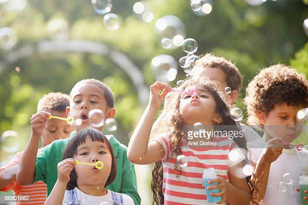 children outdoors blowing bubbles - brincar - fotografias e filmes do acervo