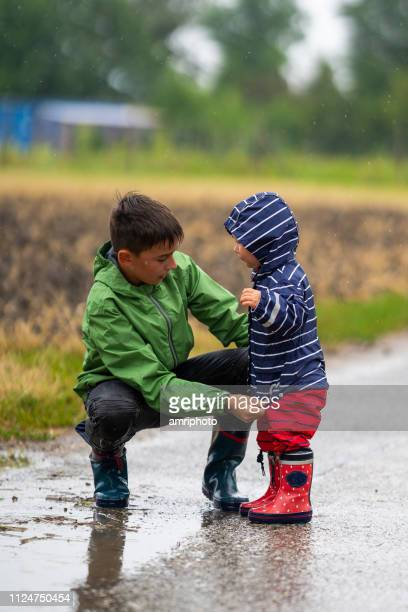 children outdoors in rain brother with little sister