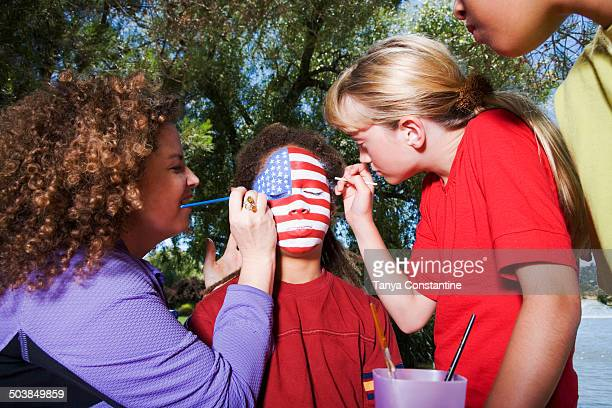 Children painting American flag on friend's face