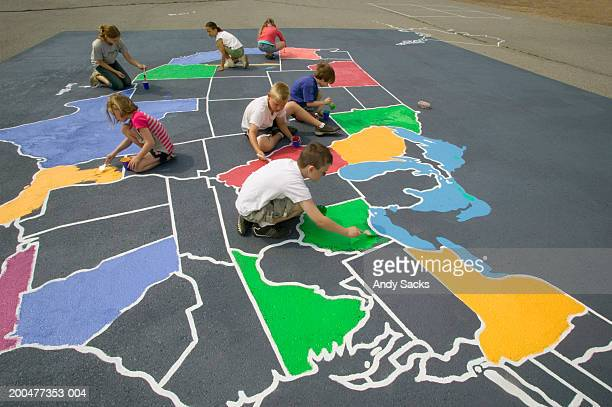 children (7-11) painting map of usa, outdoors, elevated view - rappresentare foto e immagini stock