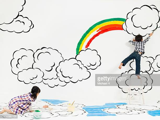 children painting rainbow and cloud on the wall - step ladder stock photos and pictures