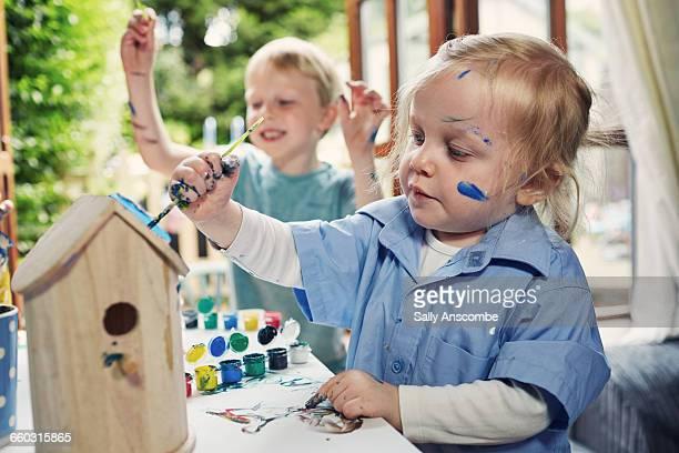 Children painting wooden birdhouses