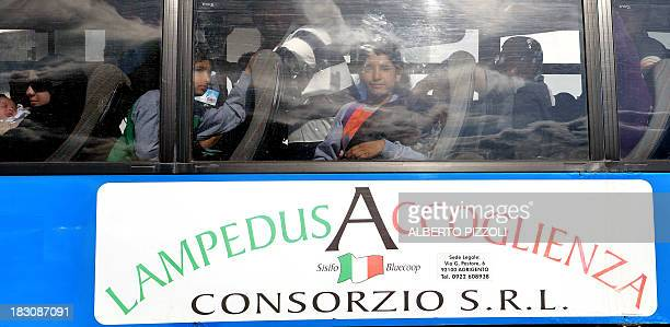 Children part of migrants arrived in Lampedusa few days ago arrive by bus in the harbour of Lampedusa to be transferred to Sicily on October 4 2013...