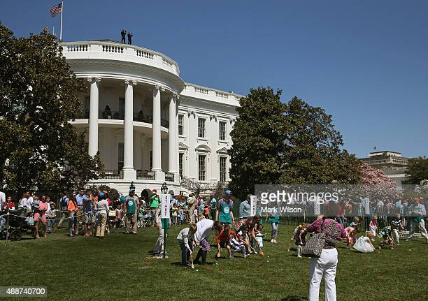 Children participate in the annual Easter Egg Roll on the south lawn as members of the US Secret Service look through high powered binoculars on the...