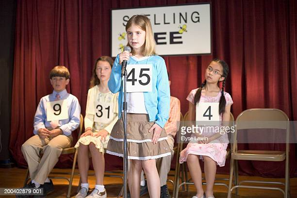 Children (7-12) participating in spelling bee, girl at microphone