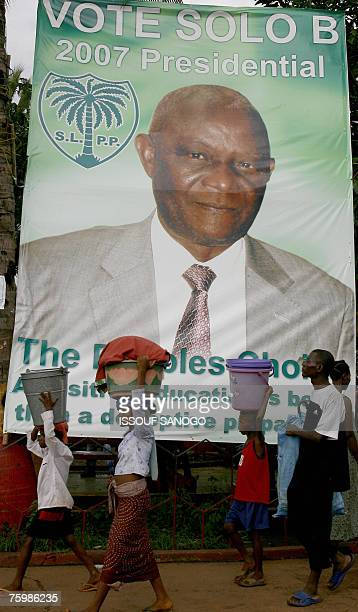 Children pass 06 August 2007 in a Freetown suburb a poster for Solomon Berewa a candidate for the ruling SLPP party ahead of presidential elections...
