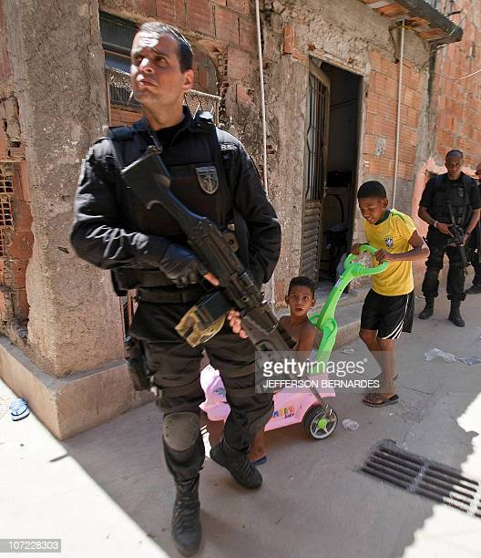 Children pass by a policeman while he patrols at Morro do Alemao shantytown on November 29 2010 in Rio de Janeiro Brazil Police scoured the sewers...
