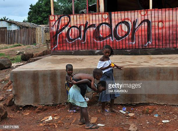 Children pass in front of a bar with an outer sign reading 'Forgiveness' in Duekoue in the West of Ivory Coast on April 20 2012 Ivory Coast President...